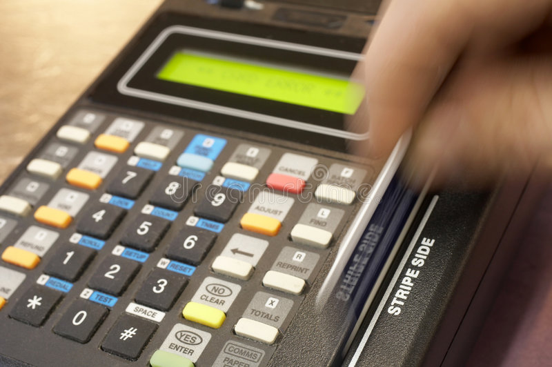 Credit card. Terminal swipe, hand in motion, DOF focus on stripe side royalty free stock photos