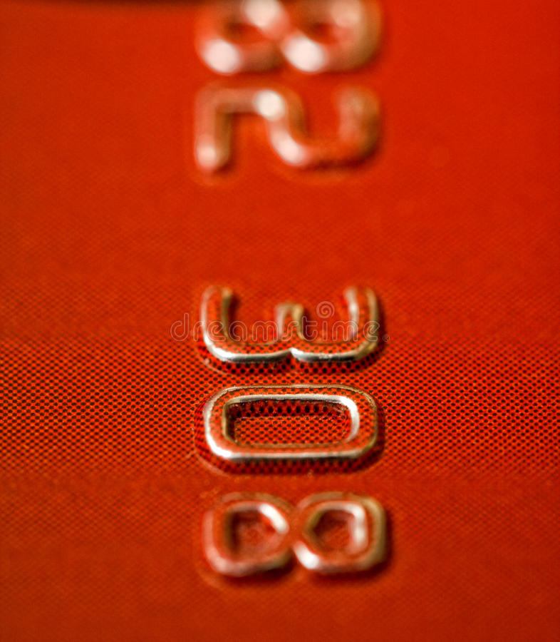 Credit card. Closeup of digits on face of red bank / debit / credit card royalty free stock images