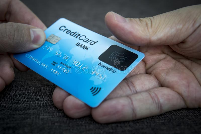 Credit card has built-in fingerprint scanner. Illustration of biometric payment security. One male hand is holding blue card and royalty free stock photography