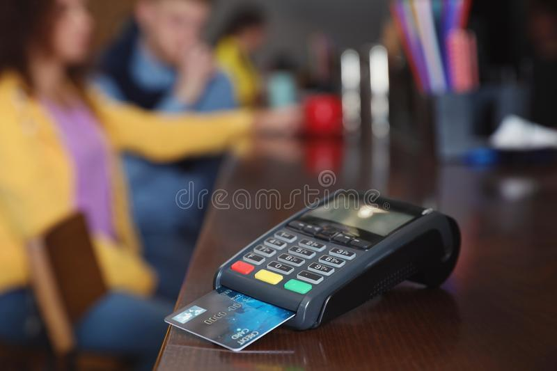 Credit card machine for non cash payment on counter in cafe. Space for text. Credit card machine for non cash payment on wooden counter in cafe. Space for text stock photo