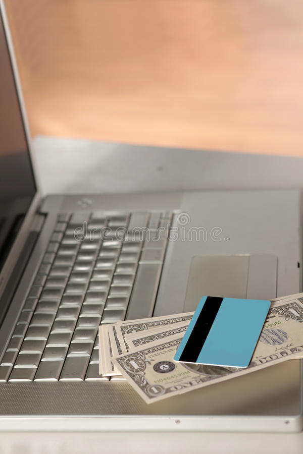 Credit card and money. On a laptop keyboard stock photo