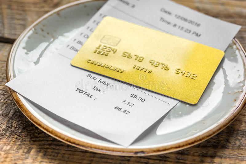 Credit card for paying, plate, glasses and check on cafe desk background. Credit card for paying, plate, glasses and check on cafe wooden desk background royalty free stock photography
