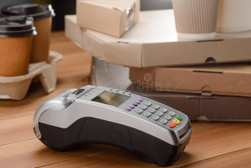 Credit card reader. Cups of coffee and pizza boxes. Take-away food and contactless payments stock image