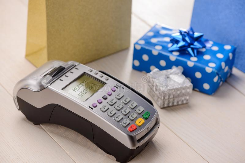 Credit card reader and gifts. On a wooden cashier`s desk. Successful payment notification and perfect holiday season royalty free stock images