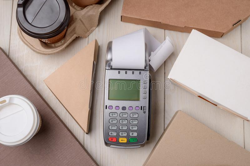 Credit card reader. With receipt, paper boxes and cups, flat lay. Paying in restaurant by card or phone royalty free stock photo