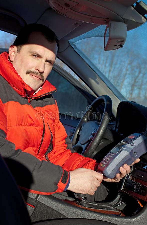Credit card reader in taxi. Drivers hand in car stock photography