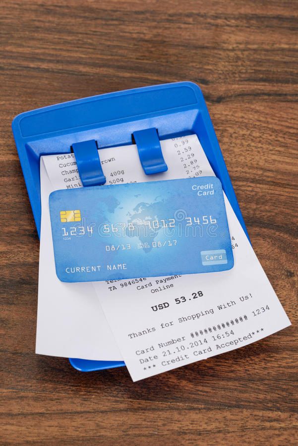 Credit card on shopping bill. Close-up Of Credit Card On Shopping Receipt Over Wooden Table royalty free stock images