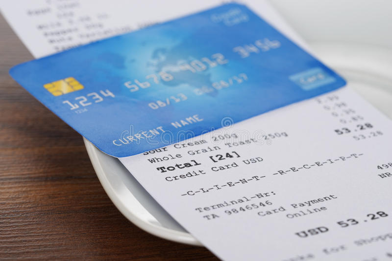 Credit card on shopping receipt. Close-up Of Credit Card On Shopping Receipt On Wooden Table royalty free stock image