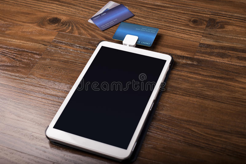 Credit Card Swipe Reader. Credit card payment on a swipe or chip reader app on a tablet used by small or online businesses. The electronic device is used as a stock image