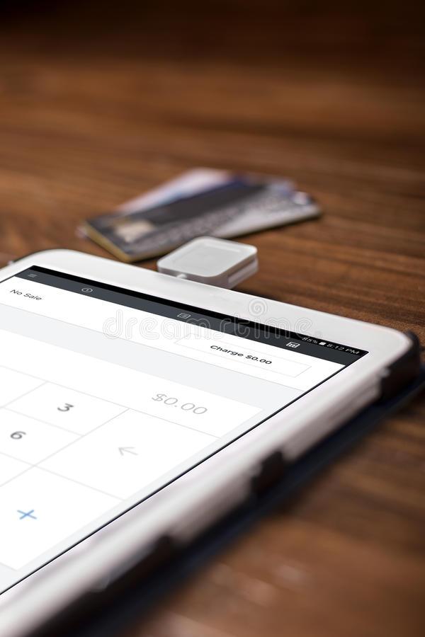 Credit Card Swipe Reader. Credit card payment on a swipe or chip reader app on a tablet used by small or online businesses. The electronic device is used as a stock photo