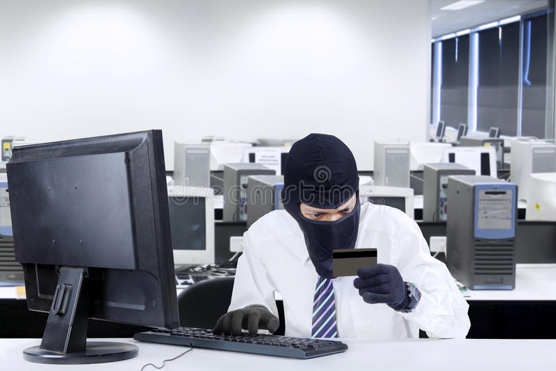 Credit card theft 1. Internet Theft - businessman wearing a mask and holding a credit card while sat behind a computer royalty free stock image