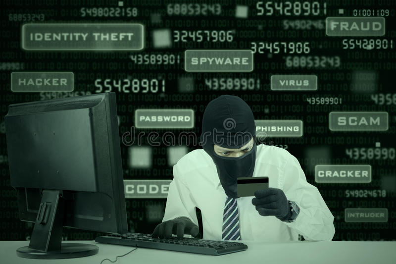 Credit card theft 2. Internet Theft - businessman wearing a mask and holding a credit card while sat behind a computer stock images
