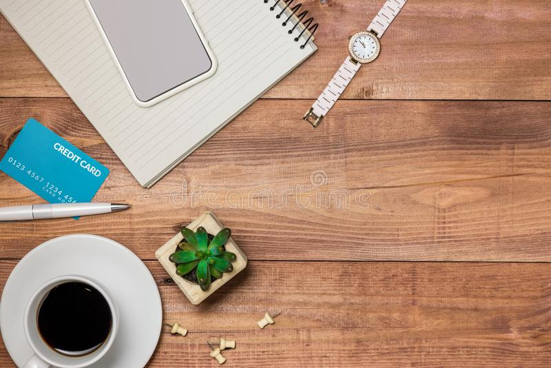 Credit card, watch, smartphone and coffee cup on wooden table.  stock photography