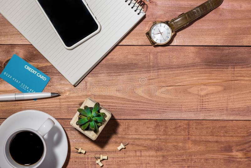 Credit card, watch, smartphone and coffee cup on wooden table.  royalty free stock photos