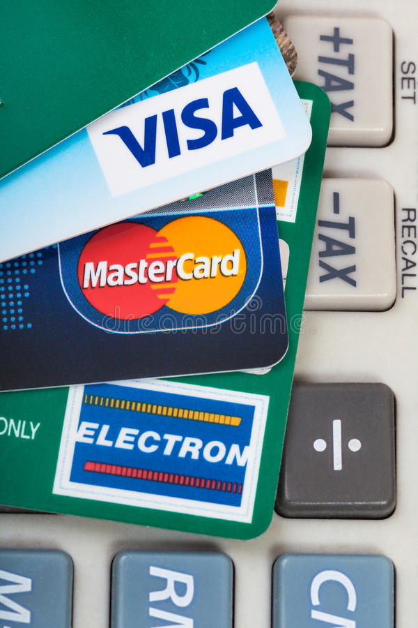 Credit cards on tax calculator keypad. MOSCOW, RUSSIA - DECEMBER 8, 2105: few plastic VISA and MasterCard, VISA ELECTRON credit and debit cards on tax calculator royalty free stock photo