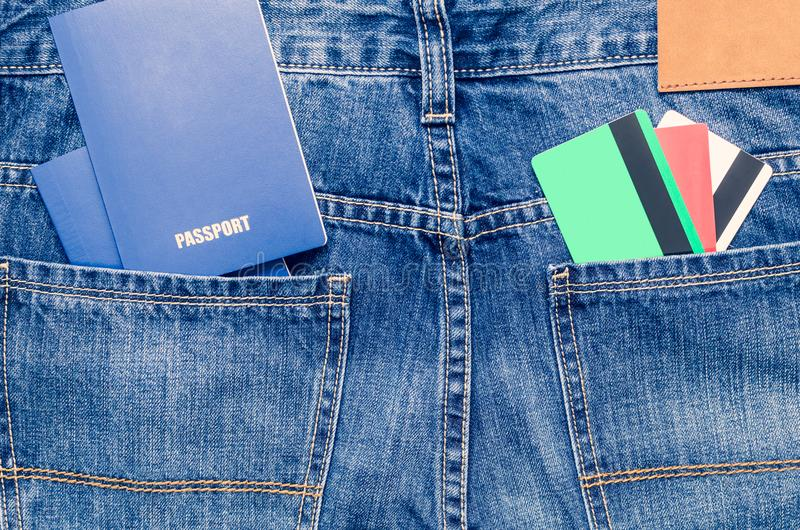 Credit cards and two blue passports in the pocket of blue jeans stock image