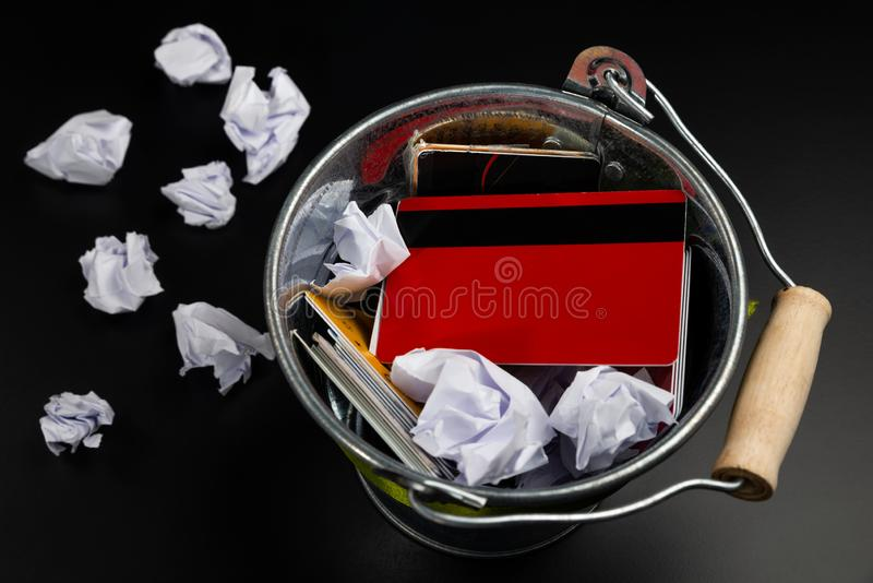 Credit/debit/shopping cards and crumpled paper are in the rubbish bin on the black background/table. Buy Nothing Day. Credit/debit/shopping cards and crumpled stock photography