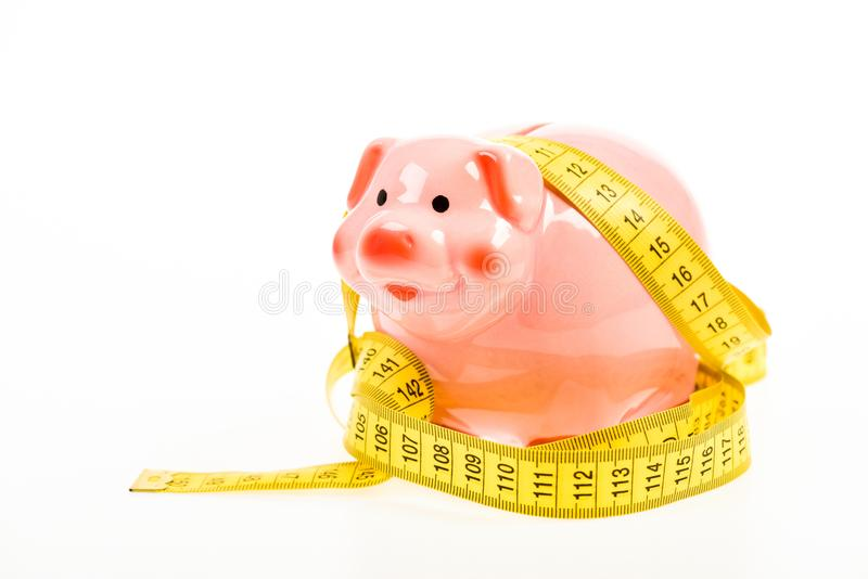 Credit loan debt. Measure costs. Piggy bank and measuring tape. Budget limit concept. Economics and finances. Pig trap stock image