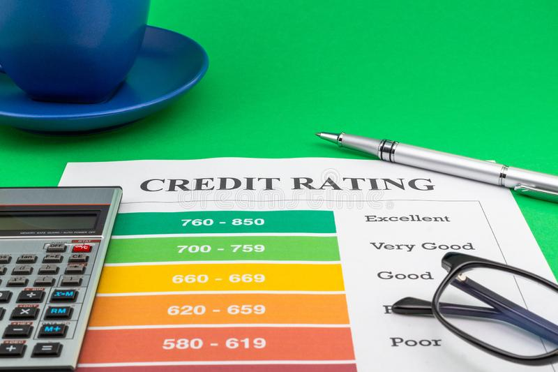 Credit rating on a green table, pen and calculator. stock images