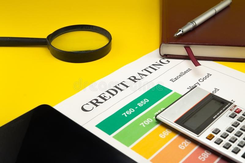 Credit rating on a yellow table, pen, magnifier, notebook stock photos