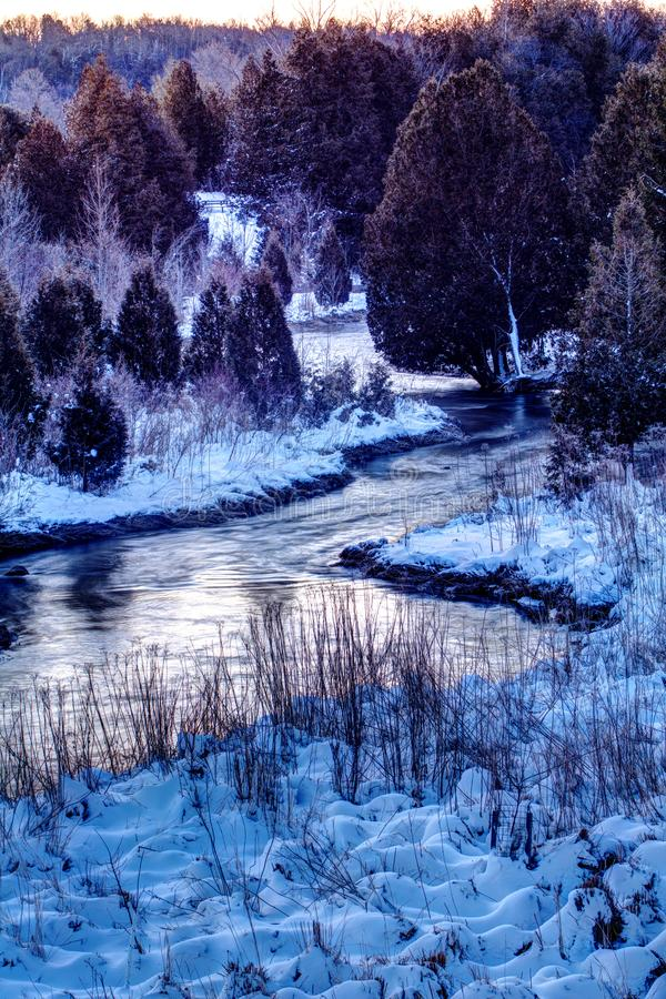 Early Morning Snowy Scene On The Credit River. The Credit River twists between the cedar trees and the snow covered ground. Location near Orangeville, Ontario stock photography