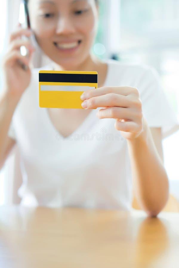creditcard ter beschikking van het vrouwelijke mobiel spreken royalty-vrije stock fotografie