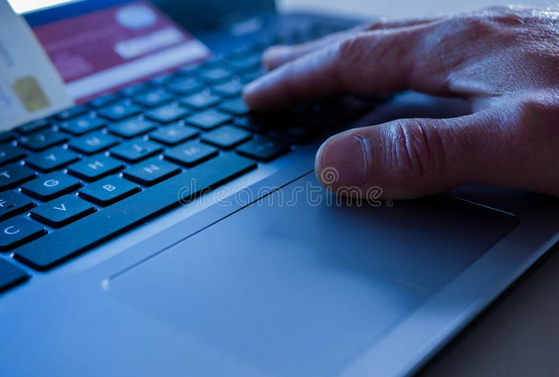 Creditcarddief die aan wachtwoorden op laptop computertoetsenbord werken, conceptueel beeld van fraude stock foto's