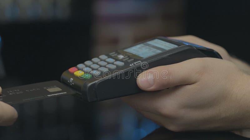 Creditcardmachine voor geldtransactie De mensenhand met creditcard jat door pos terminal en gaat speldcode in stock afbeeldingen