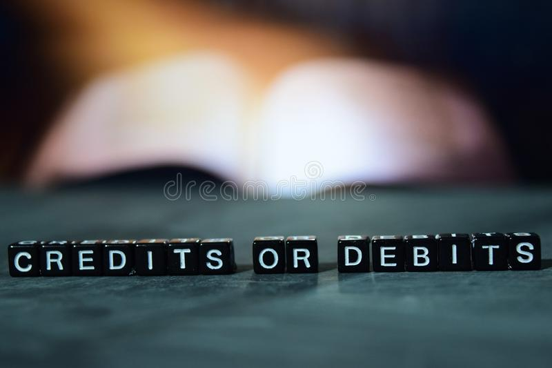 Credits or debits on wooden blocks. Business and finance concept. Cross processed image with bokeh background royalty free stock photos