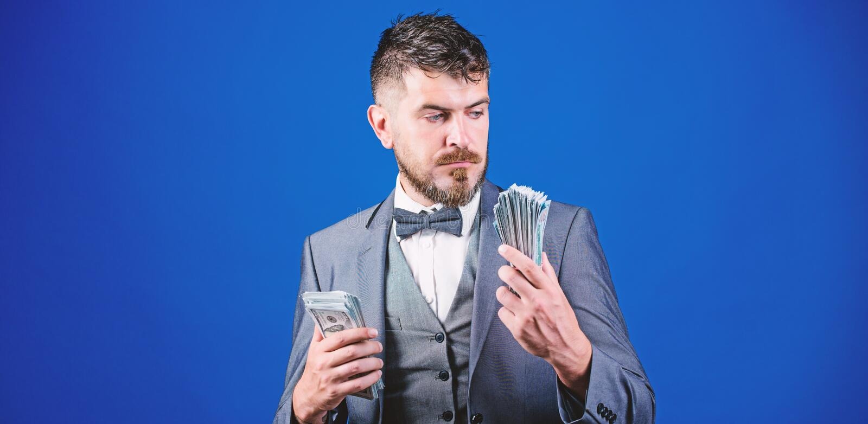 Credo in banconote Uomo barbuto che tiene denaro contante Uomo d'affari ricco con le banconote dei dollari americani Mediatore di fotografia stock libera da diritti