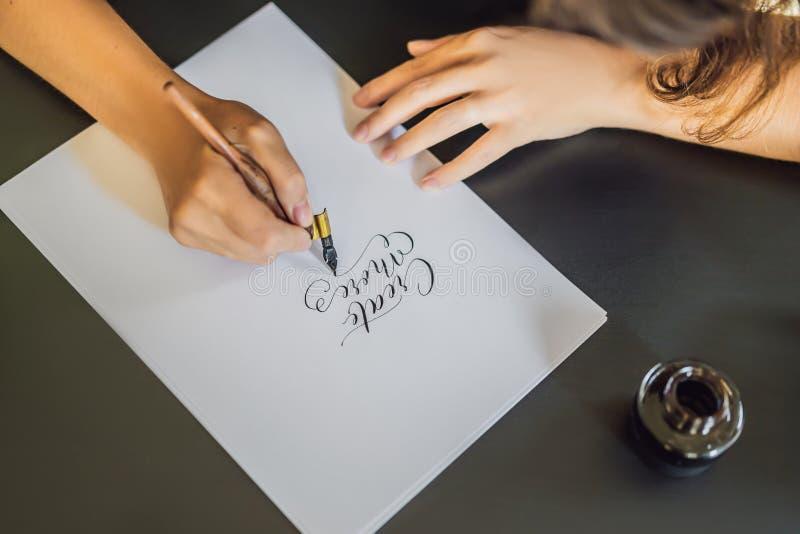 Cree más El cal?grafo Young Woman escribe frase en el Libro Blanco Inscripci?n de letras adornadas ornamentales calligraphy fotografía de archivo