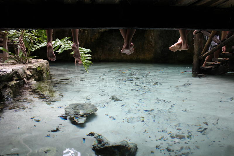 Creekside Pals. Feet dangling from a bridge over an underwater cave in Tulum, Mexico stock images