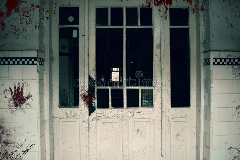 Creepy bloody door of the haunted asylum. Abandoned and decayed building of psychiatric hospital royalty free stock image