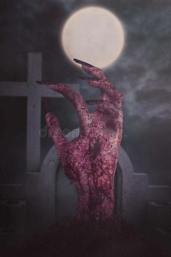 Creepy bloody zombie hand at cemetery. Image of creepy bloody zombie hand with long nails coming out from cemetery at dark night stock image