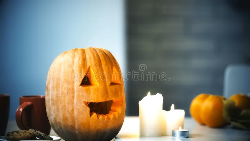Creepy carved Halloween pumpkin smiling with flamed candles on table, traditions royalty free stock photography