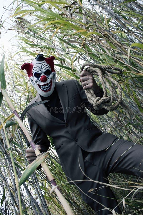 Creepy clown having fun. Scary killer royalty free stock photography