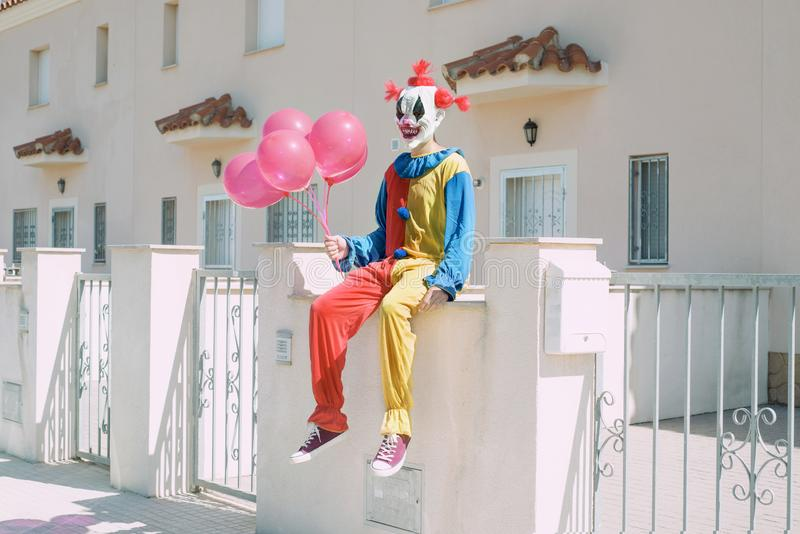 Scary clown with a bunch of balloons outdoors. A creepy clown wearing a colorful yellow, red and blue costume, holding a bunch of red balloons in his hand royalty free stock photo