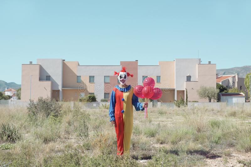 Scary clown with a bunch of balloons outdoors. A creepy clown wearing a colorful yellow, red and blue costume outdoors, holding a bunch of red balloons in his stock photo