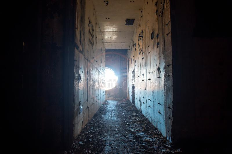 Creepy corridor in abandoned nuclear power plant with light from round hole royalty free stock images