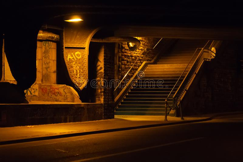 Creepy, dimly lit underpass below an iron bridge. Creepy, dimly lit underpass with grafiti below an iron bridge stock image