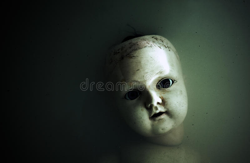 Creepy doll face in dark water stock photography
