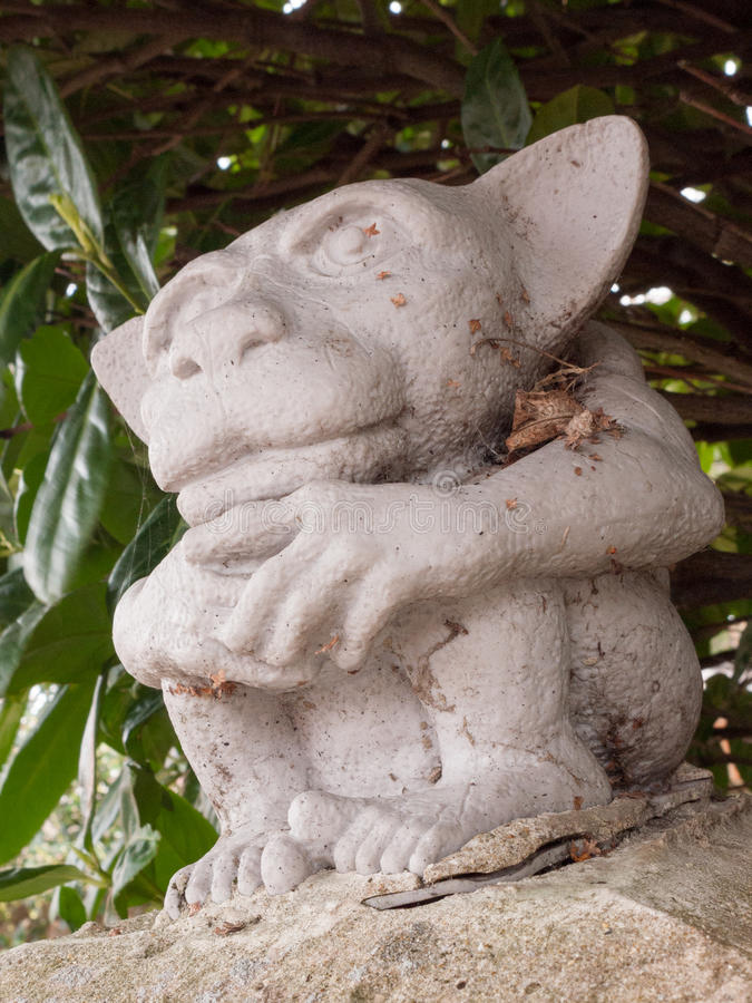 A Creepy Gremlin Statue Sitting Guard on the Wall. A creepy but funny little gremlin statue stock image
