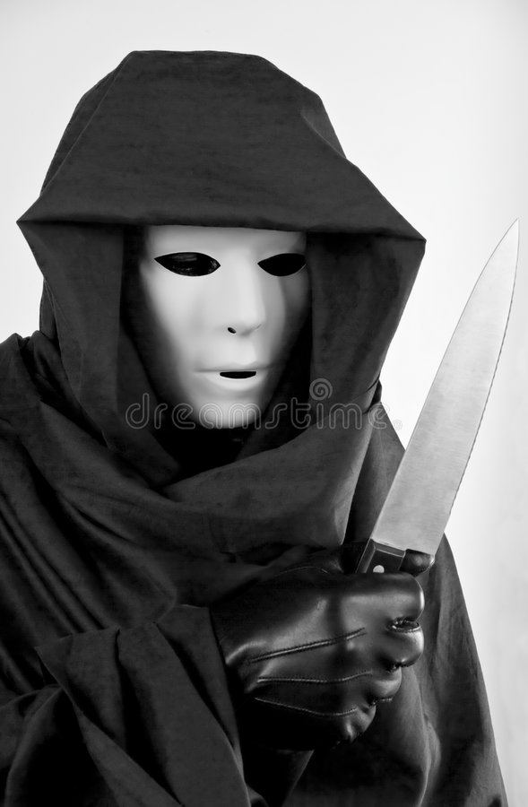Creepy Halloween. A man in a mask and hooded cloak, holding a carving knife in a creepy, frightening stance stock image