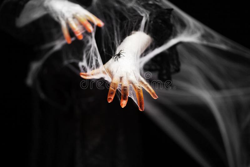 Creepy halloween hand in orange and white with spider web, zombie hand stock photography