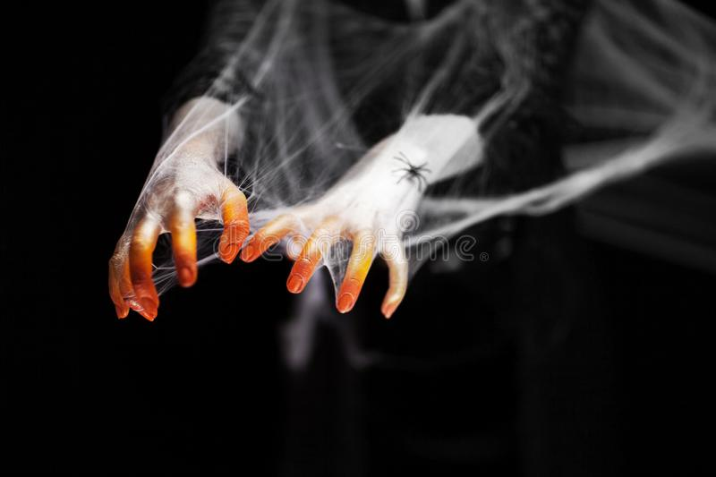 Creepy halloween hand in orange and white with spider web, zombie hand royalty free stock images