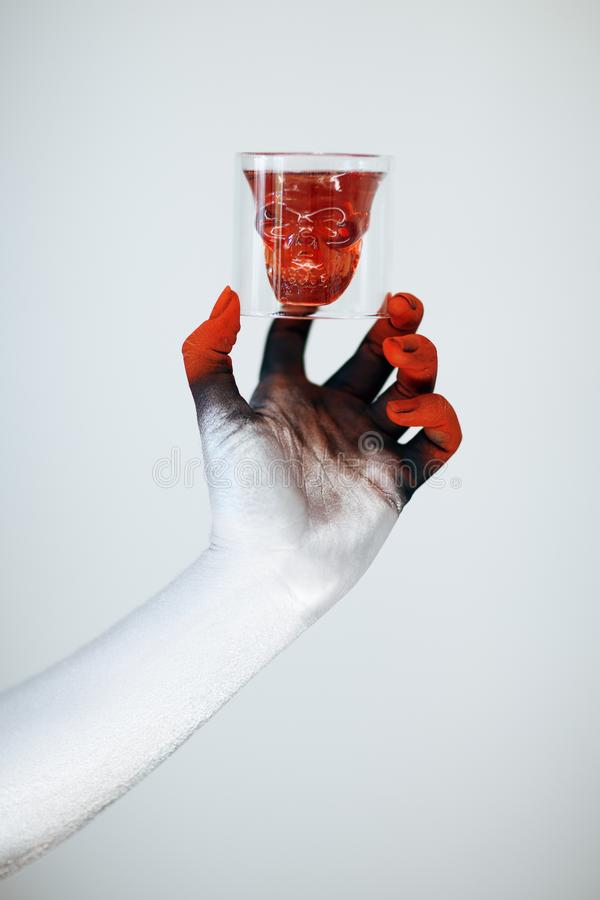 Creepy Halloween monster hand with white, red and black make up holding glass with skull of blood stock images