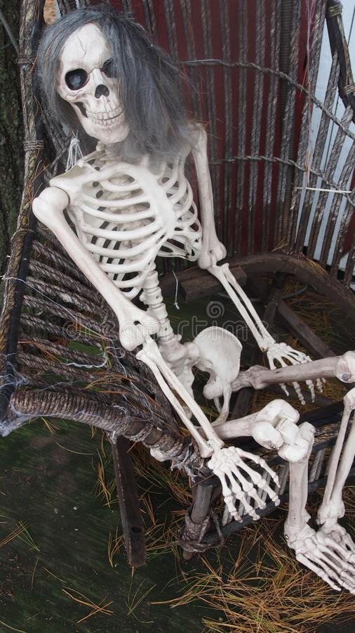 Creepy halloween skeleton on a chair. Creepy halloween skeleton sitting on a old braided chair stock photography