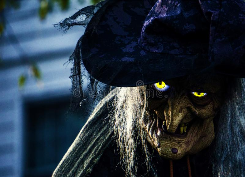 Creepy Halloween Witch with glowing eyes. A very creepy Halloween Witch decoration with yellow glowing eyes. Her hat and hair add to the feel of this scary royalty free stock image