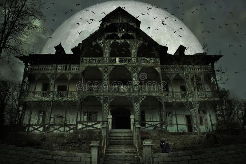 Creepy haunted house with dark horror atmosphere. A black cat, many bats and big full moon behind the frightful scene stock photography