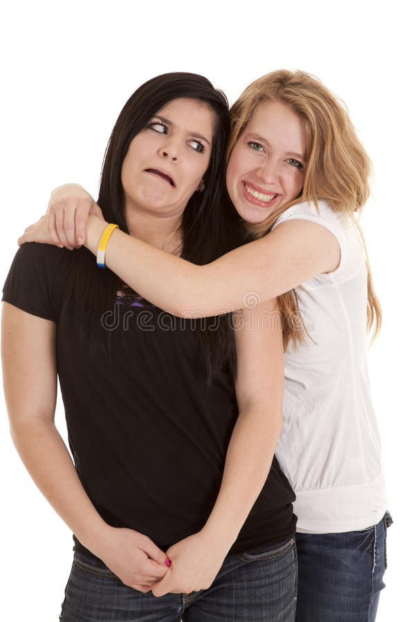 Creepy hug. A teenage girl has a funny expression on her face when another teen is hugging on her royalty free stock images